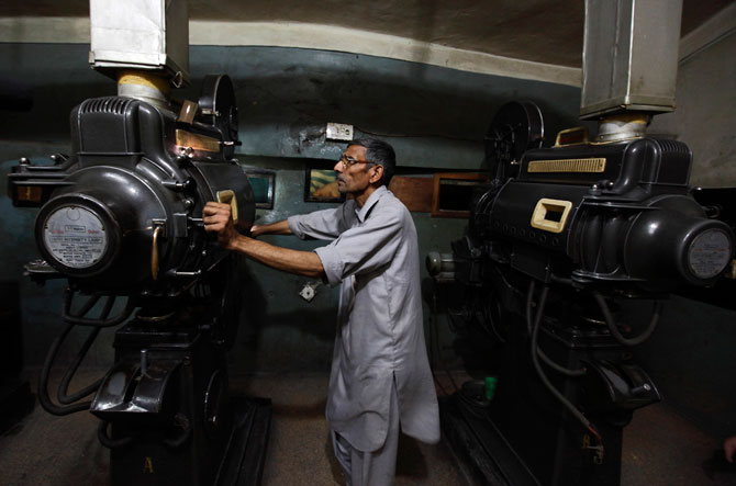A worker checks a strip of an old Pashto movie loaded into a projector at Arshad cinema in Peshawar.