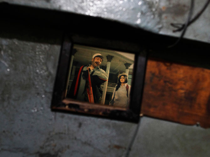 A scene of an old Pashto movie is seen through a window at Arshad cinema.