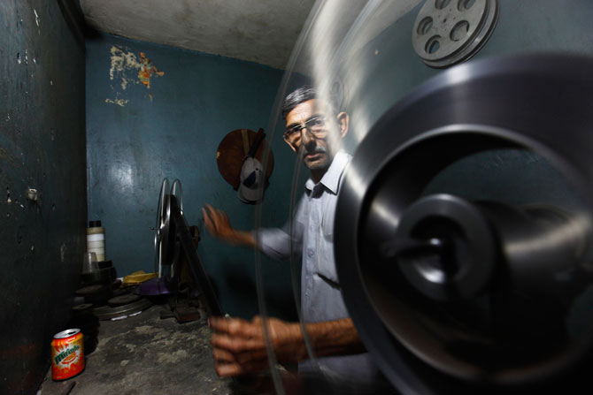 A worker prepares a strip of an old Pashto movie before loading it into a projector. - Photo by Reuters