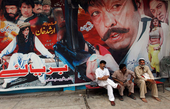 Cinema workers sit near a poster of a Pashto movie. - Photo by Reuters
