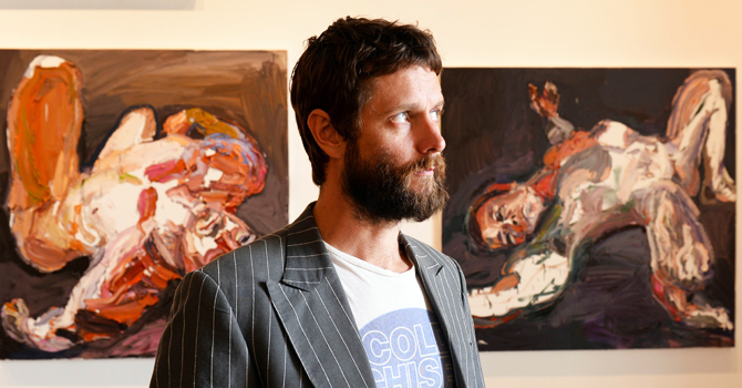 Australian war artist Ben Quilty standing in front of some of his paintings of soldiers in a Sydney art gallery. —AFP PHOTO