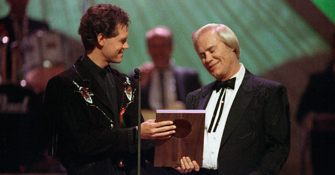 Jones accepts his Country Music Hall of Fame award from Randy Travis, left, during the Country Music Association Awards show in 1992. —Photo (File) AP