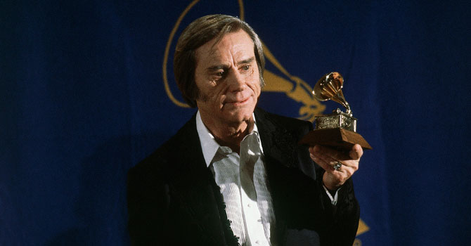"George Jones poses with the Grammy he won for best male country vocal performance of ""He Stopped Loving Her Today"". —Photo (File) AP"