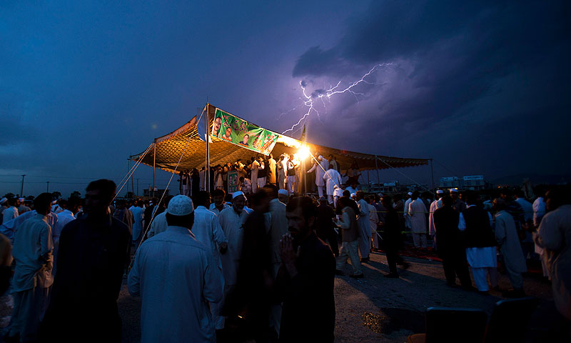 Lightning flashes as political supporters of the Pakistan Muslim League hold a meeting under tight security due to ongoing attacks on political rallies and parties' election offices, in Islamabad. -Photo by AP