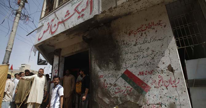 Men stand outside the campaign office of the Muttahida Qaumi Movement (MQM) political party, after a bomb blast in Karachi.  — Photo by Reuters