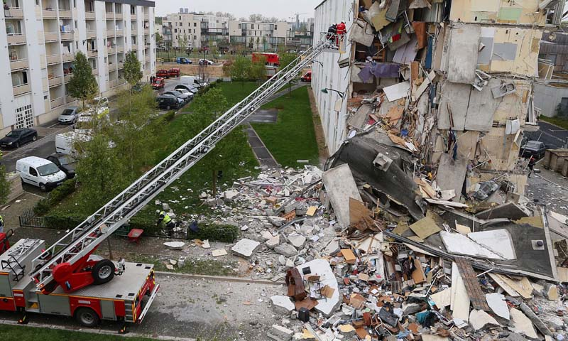 Firemen are at work near the collapsed section of an apartment building on April 28, 2013 in Reims, eastern France, after a suspected gas explosion killed at least two people and injured nine others. —Photo AFP