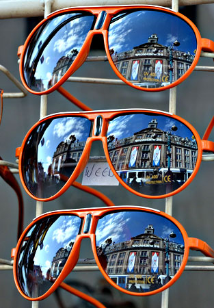 Orange sunglasses on sale in a shop in central Amsterdam on April 29, 2013 on the eve of the investiture of the country's new King. Dutch Queen Beatrix, who ruled the Netherlands for 33 years, announced on January 28, 2013 her abdication from the throne in favour of her son, Prince Willem-Alexander. — AFP Photo