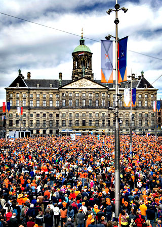 People, most of them wearing orange tee shirts, hats or plastic crowns, gather on April 30, 2013 at the Dam Square in Amsterdam, The Netherlands, to attend the investiture of the country's new King. — AFP Photo