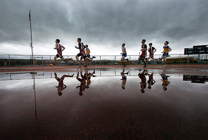 A pack of runners from Valley View High School and Scranton High School sprint past a rain puddle during the 800-meter event during athletics meet at Scranton High School on Monday, April 29, 2013 in Scranton, Pa. — AP Photo