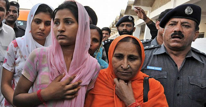 A Pakistani police man escorts family members of Indian prisoner held in Pakistan, Sarabjit Singh, Dalbir Kaur his sister (2-R) and daughters Swapandip (C) and Poonam (L) upon their arrival at The Kot Lakhpat Central Jail to meet him in Lahore. — File Photo by AFP