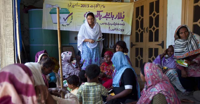 In this Monday, April 29, 2013 photo, Ruksana Ali, centre, an activist from the Association for Gender Awareness & Human Empowerment delivers a lecture about the benefits of voting in Mateela village near Sargodha, Pakistan. - AP Photo