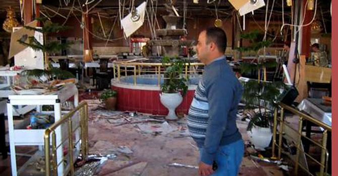 An Iraqi man looks at the damage a bomb wrecked in a restaurant.—File Photo by AFP