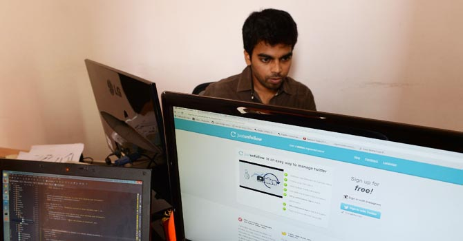 """Indian software developer and entrepreneur Nischal Shetty (R), who developed Twitter application """"justunfollow"""", poses in his office in Vashi on the outskirts of Mumbai. —Photo by AFP"""