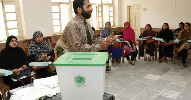 An Election Commission of Pakistan staffer giving training to polling officers at a local college. — Photo by INP