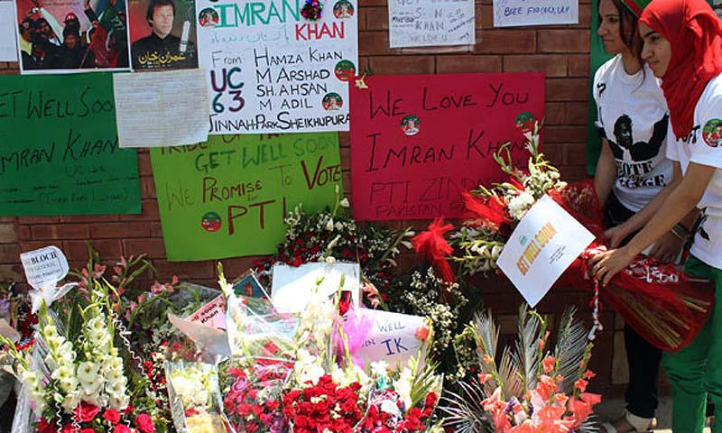 Supporters of Pakistani politician and former cricketer Imran Khan, place flowers outside a hospital where Khan is admitted in Lahore on May 8, 2013. — Photo by AFP