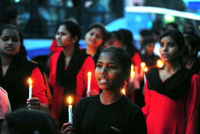 "Members of ""Red Brigade"" shout slogans and carry placards as they take part in a candlelight protest in Lucknow."