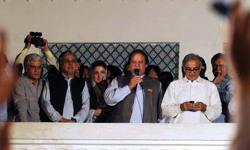 Former Pakistani Prime Minister and head of the Pakistan Muslim League-N (PML-N) Nawaz Sharif (C) is flanked by his brother Shahbaz Sharif (R) as he addresses the supporters after his party victory in general election in Lahore on May 11, 2013. — Photo AFP