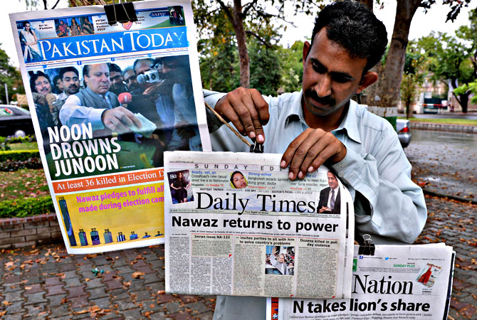 A Pakistani vendor arranges morning newspapers with front-page-coverage of former Pakistani Prime Minister Nawaz Sharif's success in landmark elections the day before, along a roadside stall in Islamabad on May 12, 2013.— AFP Photo
