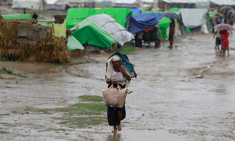 A woman from the Thandawli village uses an broken umbrella to shelter herself from the rain in a Rohingya internally displaced persons (IDP) camp outside of Sittwe, May 14, 2013. — Photo Reuters