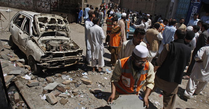 People gather at the site of an explosion outside an election office of a candidate in Peshawar, Pakistan, Sunday, April 28, 2013. — AP Photo.