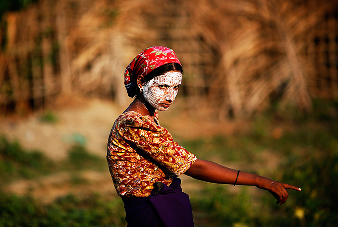 A Rohingya Muslim woman wearing traditional thanaka paste on her face gestures in a camp for people displaced by violence. — Reuters Photo