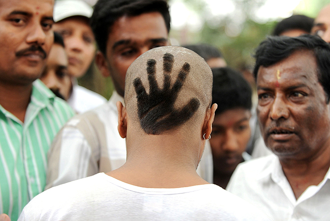 A Congress Party supporter displays his hair style featuring the party's symbol at the swearing-in ceremony of Karnataka Pradesh Congress Committee (KPCC) chief, Siddaramaiah as Karnataka chief minister in Bangalore on May 13, 2013. Congress leader Siddaramaiah takes over as 22nd Karnataka chief minister after leading his party to a huge win in last week's assembly elections, winning 121 seats in the 224-seat assembly. — AFP Photo
