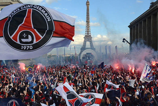 Paris Saint-Germain's supporters cheer as their team parades on a bus, on May 13, 2013 in Paris, one day after Paris secured French L1 football championship title. — AFP Photo