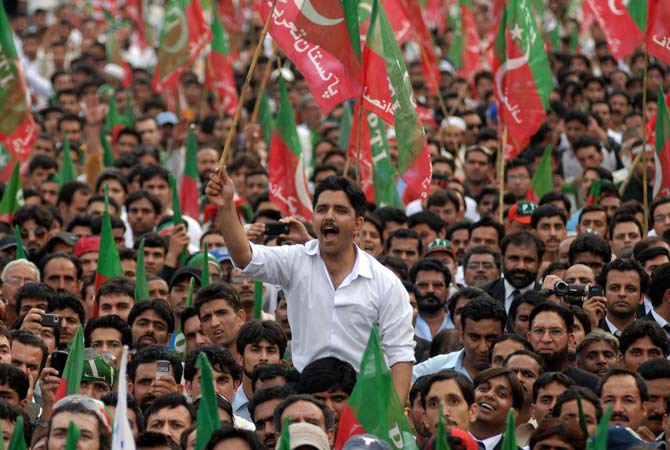 Supporters of PTI chief Imran Khan shout slogans during a rally, May 6, 2012. — Photo by AFP/File