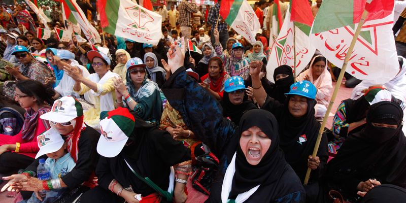 A female supporter of the MQM shouts slogans while others wave flags during a sit in protest in front of the ECP office in Karachi, May 15, 2013. The supporters were protesting against what they said was vote rigging in some polling stations during the general elections. — Reuters Photo.