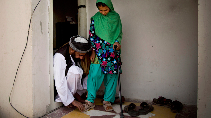 Eleven-year-old Zardana, is helped with her sandals by her father Samiullah after an interview in Kandahar, Afghanistan on Monday, April 22, 2013. She recounted the night of March 11, 2012 when a U.S. soldier attacked their family home, shooting her in the head and killing 11 relatives. She suffered nerve damage on her left side and has to walk with a cane. Her hand is too weak to hold anything heavy.  — AP Photo.