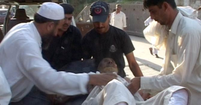 Rescue workers helping a man injured in the blast in Malakand. -Photo by Zahir Shah Sherazi