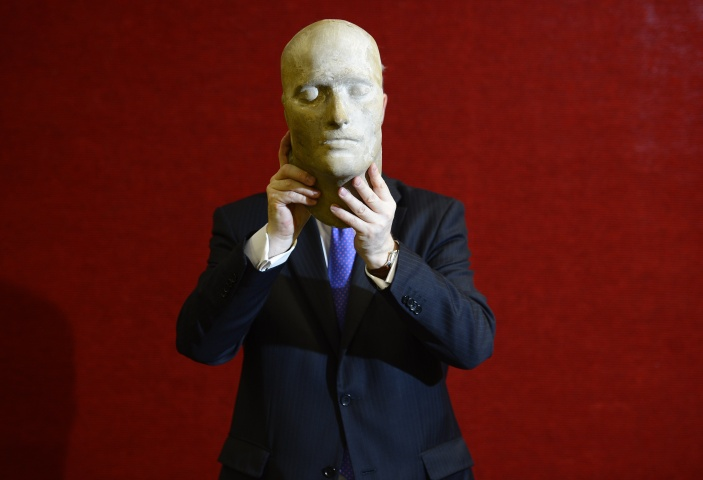 worker poses with the death mask of the French Emperor Napoleon Bonaparte, at Bonhams auction house in London May 17, 2013.