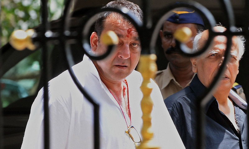 Indian Bollywood actor Sanjay Dutt (C) and film director Mahesh Bhatt (R) leave Dutt's residence to surrender to a special Terrorist and Disruptive Activities (TADA) court  in Mumbai on May 16, 2013. —AFP Photo