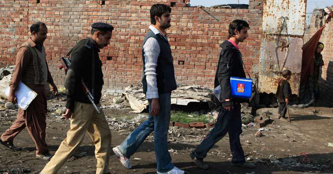 A police officer escorts health workers during a visit to Lahore's slums in an anti-polio campaign. — File Photo by AP.