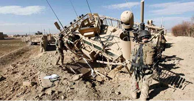 US Army soldiers inspect the scene after an IED (improvised explosive device) blast during a road clearance patrol in Logar province, eastern Afghanistan. — File Photo by Reuters