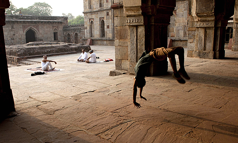 "Indian dancer Om Dubey, 20, practices his moves as elderly yoga practitioners sit in the courtyard in front of the Three Domed Mosque and the Bada Gumbad monument, built during the reign of Sikander Lodi in 1494, at Lodi Gardens in New Delhi on May 7, 2013. India's youth, comprising some 41 per cent of its 1.2 billion population based on a 2001 census; represent what population experts call the ""demographic dividend"" of young workers that the government hopes will help power the country's economy. — AFP Photo"