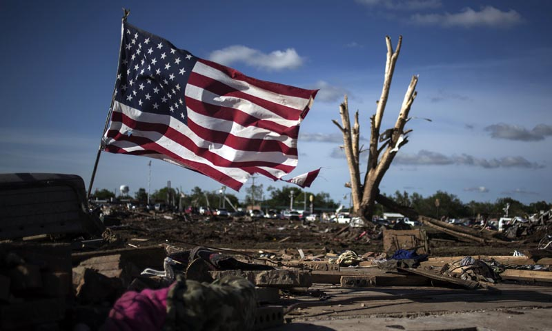 A flag is placed in the foundation of a flattened home day after a tornado devastated the town Moore, Oklahoma, in the outskirts of Oklahoma City May 21, 2013. — Photo Reuters