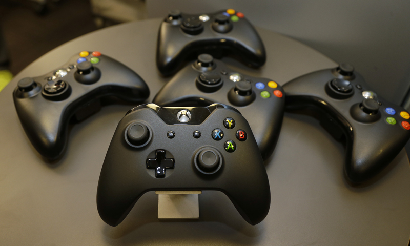 The new controller for Microsoft's Xbox One entertainment and gaming console system is shown front and center with older- controllers behind it, in Redmond. — AP Photo
