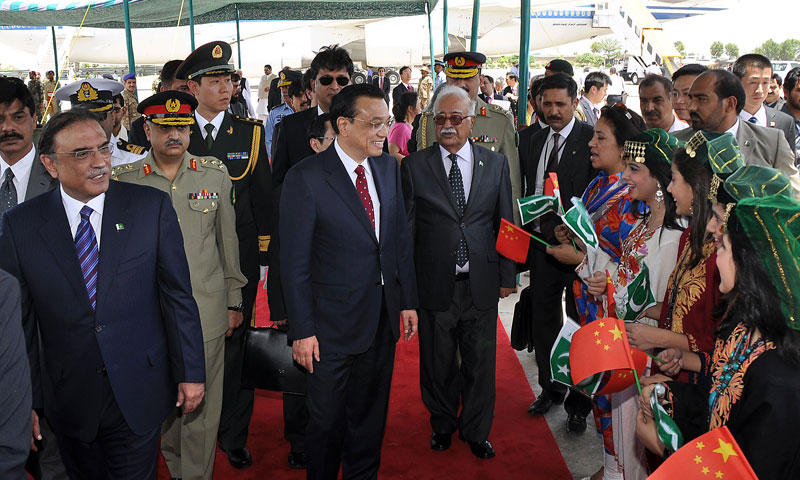 Chinese Premier Li Keqiang (C), flanked by President Asif Ali Zardari and caretaker premier Mir Hazar Khan Khoso is welcomed by hostesses bearing Chinese flags upon his arrival at Pakistan's Nur Khan air base in Rawalpindi on May 22, 2013. — Photo by AFP