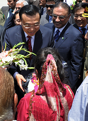 Chinese Premier Li Keqiang (L), flanked by Pakistani President Asif Ali Zardari (2nd R), receives flowers upon his arrival at the Pakistan's Nur Khan air base in Rawalpindi on May 22, 2013. — AFP Photo