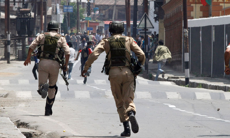 Indian policemen chase Kashmiri protesters in Srinagar, May 21, 2013. — Photo by AP