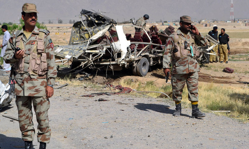 Pakistani security officials keep watch near a destroyed vehicle used by security forces following a bomb attack on the outskirts of Quett, on May 23, 2013.