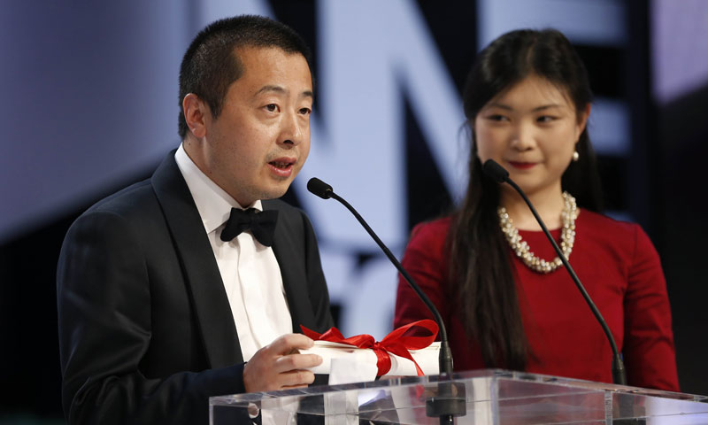 "Chinese director Jia Zhangke (L) speaks on stage on May 26, 2013 after being awarded with the Best Screenplay award for the film ""A Touch of SIn"" during the closing ceremony of the 66th Cannes film festival in Cannes.—File Photo."