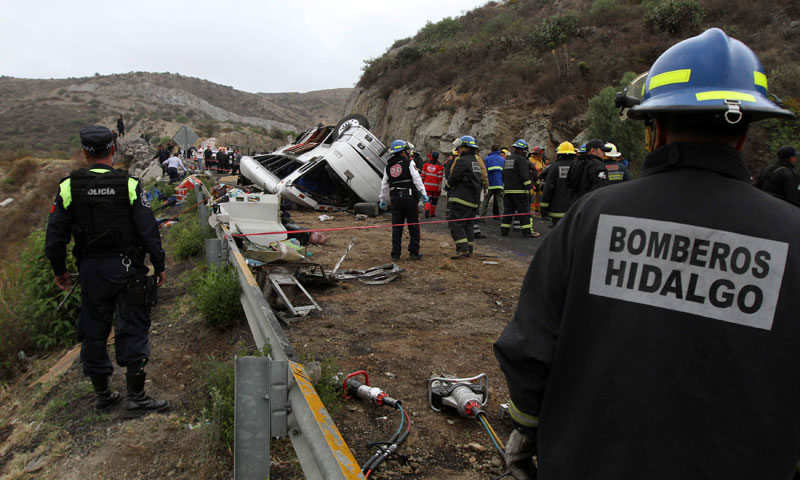 Rescue workers and firefighters stand near the wreckage of an overturned tour bus in Real del Monte, on the outskirts of Pachuca, May 26, 2013. — Photo by Reuters