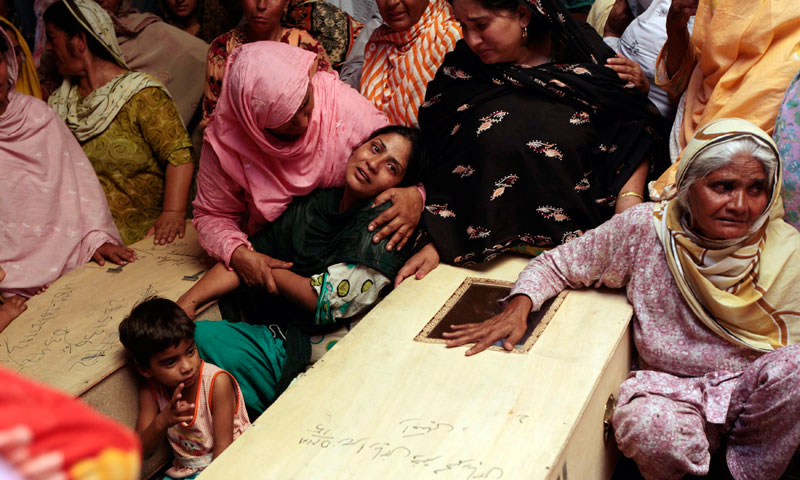 A woman mourns near a child's casket on the outskirts of Gujrat, 100 miles southeast of Islamabad, May 25, 2013. — Photo by Reuters
