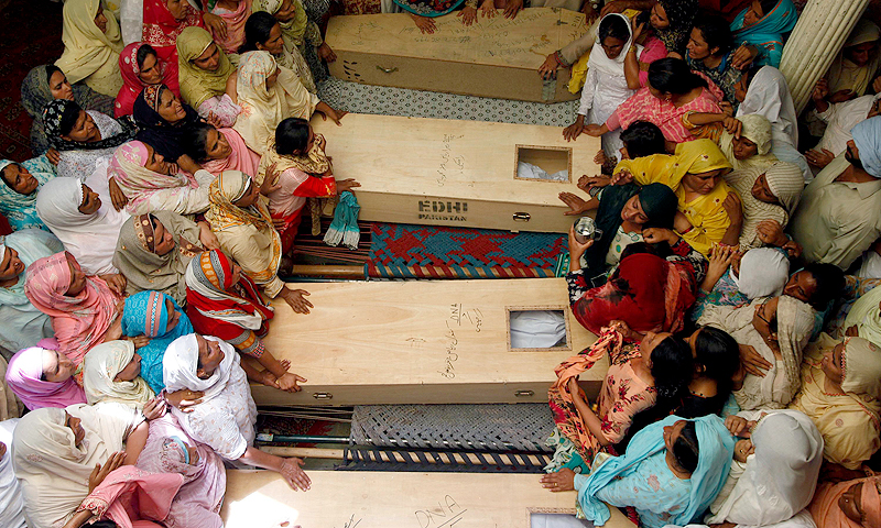 Relatives of 14 children, who died after a gas cylinder exploded on a school bus, mourn over their coffins, on the outskirts of Gujrat, 100 miles (170 km) southeast of Islamabad. — Reuters Photo