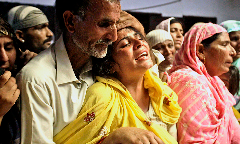 A Pakistani man comforts his relative mourning the death of a family member. — AP Photo