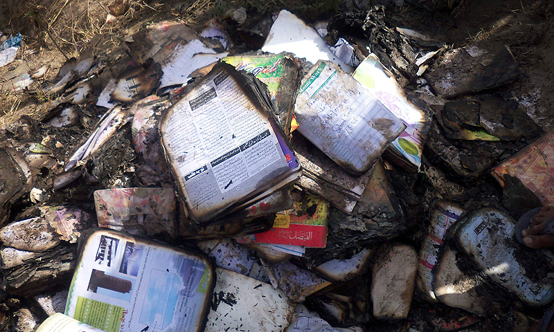 Burnt school books are seen near a school bus, on which a gas cylinder exploded. — Reuters Photo