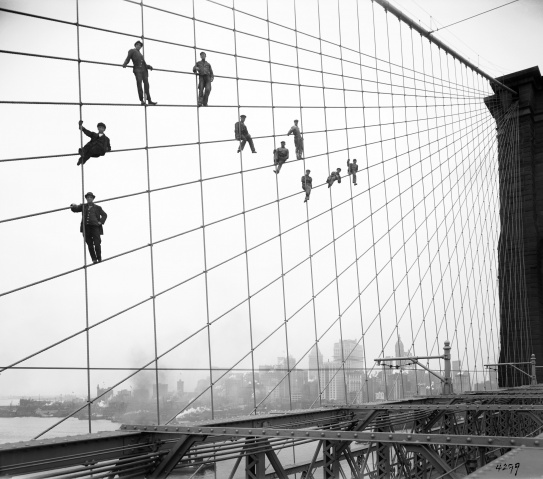 In this Oct. 7, 1914 photo provided by the New York City Municipal Archives, painters are suspended from wires on the Brooklyn Bridge in New York.— AP Photo