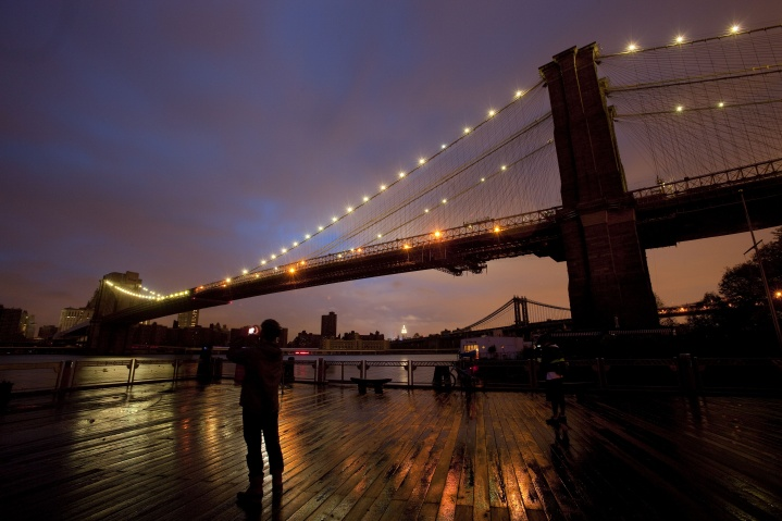 People stop along the Brooklyn waterfront to photograph the Brooklyn Bridge and the Manhattan skyline, Tuesday, Oct. 30, 2012 in New York.— AP Photo